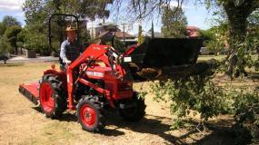 A Kubota L1501DT 18hp diesel 4WD with 4-in-1 front end loader in action.