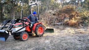 John Hughson operates his remanufactured Kubota tractor on his block.