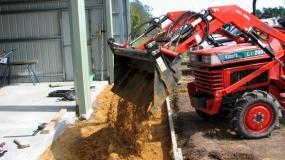 Ken Gray on his Kubota L1-20DT, transporting sand with the 4-in-1 loader.