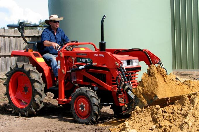 Ken Gray on his Kubota L1-20DT transporting sand with the 4-in-1 loader.