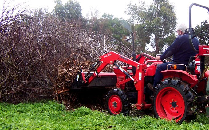 Moving tree litter with the AGMAX 4-in-1 bucket.