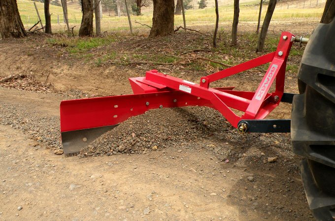 Spreading gravel with an AGMAX grader blade is much quicker than using a shovel.